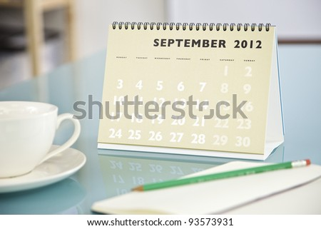 Desktop calendar sitting on a glass desk showing the month of September 2012 - stock photo