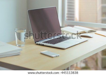 Desktop manager in a large company, Wooden desk with modern laptop, glass of water, modern cell phone, notebook. Desktop with a view of downtown, Sunrise, Shallow DOF. - stock photo