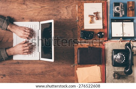 Desktop top view with male hands working on a contemporary laptop on the left and vintage objects and items on the right - stock photo