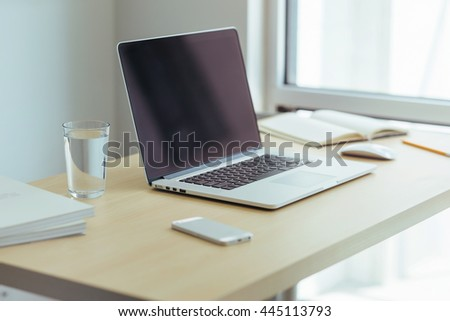 Desktop with a view of downtown, Sunrise, Shallow DOF. Wooden desk with modern laptop, glass of water, modern cell phone, notebook.