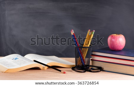 Desktop with books, pencils, apple, reading glasses and blank blackboard in background. Selective focus on front part of desk objects.