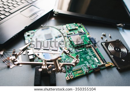 Desktop with broken disassembled laptop. Electronic parts of pc: motherboard, display (monitor), hdd. Analysis computer ram (memory) through magnifying glass. - stock photo