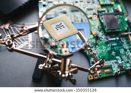 Desktop with broken disassembled laptop. Electronic parts of pc: motherboard, microprocessor. Analysis computer cpu through magnifying glass. - stock photo