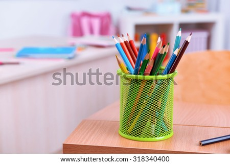 Desktop with cup of crayons in classroom - stock photo