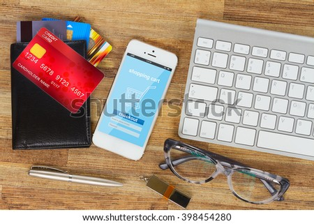 desktop with internet store page on mobile  phone and wallet with plastic cards - stock photo