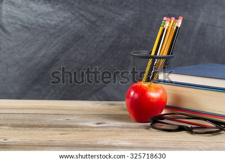 Desktop with reading materials and red apple in front of blackboard. Layout in horizontal format with copy space.  - stock photo