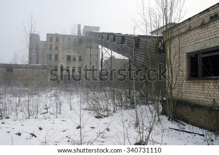 Desolate industrial soviet factory in winter time - stock photo