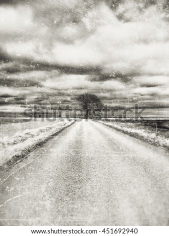 Desolate road in soft sepia tones with a lonely tree against a dark bad weather sky in the horizon.  - stock photo
