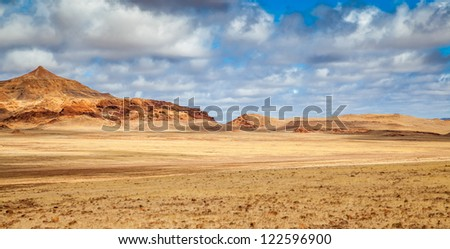 Desolation in Damaraland, Namibia, the savannah meets the hills in the distance.
