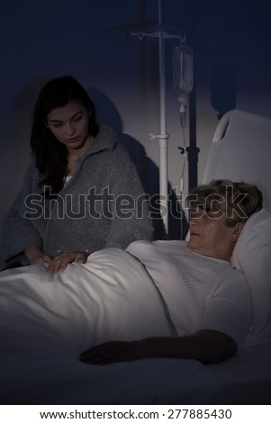 Despair daughter caring about terminally ill mother - stock photo