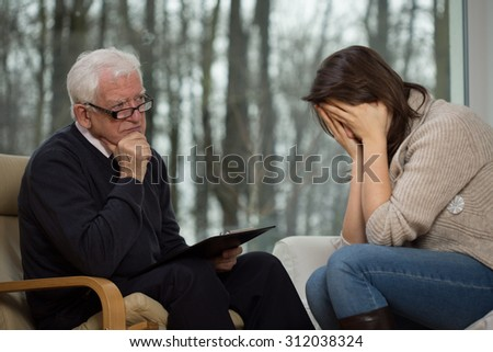 Despair young woman crying during psychological therapy - stock photo