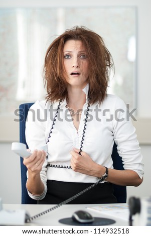 Despaired businesswoman sits at her desk with the phone in her hand. - stock photo
