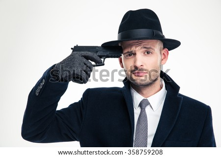 Despaired man in black coat, hat and gloves put gun to his temple over white background - stock photo