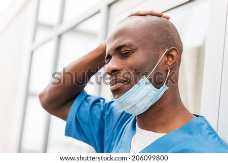 Despaired surgeon. Depressed young African doctor in blue uniform touching head with hand and keeping eyes closed while leaning at the glass door - stock photo