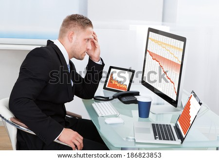 Despairing businessman faced with financial losses sitting at his desk consulting three graphs on different monitors all dropping into the red
