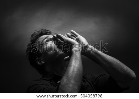 Despairing man screaming. Low key black and white portrait