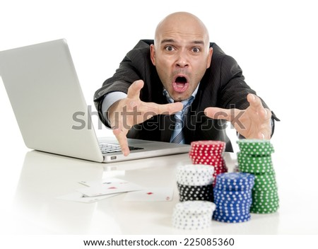 desperate addict businessman on computer laptop loosing lots of money betting on internet poker with cards and chips on online gambling addiction isolated on white background - stock photo
