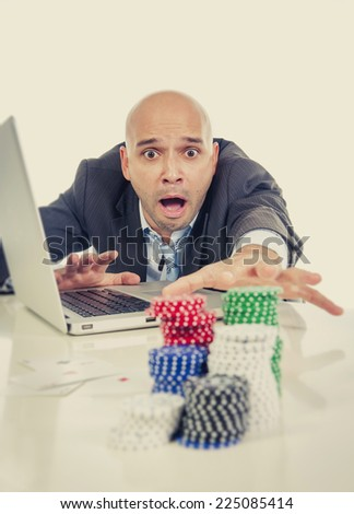 desperate addict businessman on computer laptop loosing lots of money betting on internet poker with cards and chips on online gambling addiction isolated - stock photo