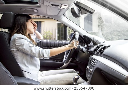 Desperate and sad woman in her car. - stock photo