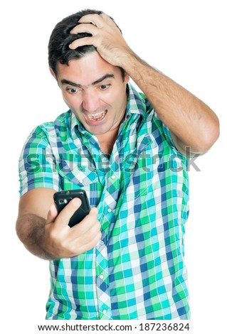 Desperate angry man looking at his mobile phone with a furious expression (isolated on white) - stock photo