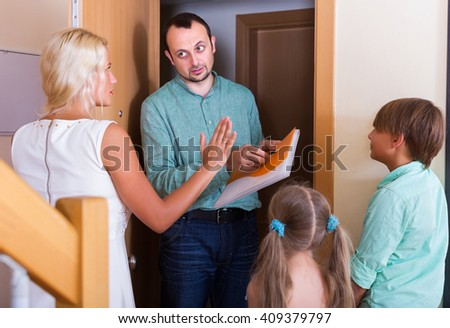 Desperate big family and irritated inspector having conversation at entrance
