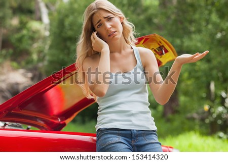 Desperate blonde calling for assistance after breaking down with her cabriolet - stock photo