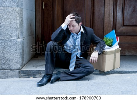 desperate business man in stress fired from job sitting on edgy street corner with office belongings in cardboard box  - stock photo