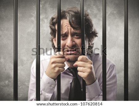 Desperate businessman behind bars - stock photo