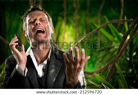 Desperate businessman lost in jungle calling for help with mobile phone. - stock photo