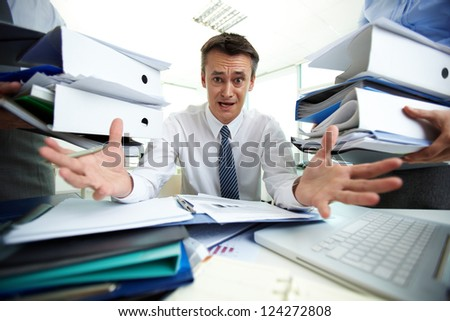 Desperate businessman not knowing what to do with all paperwork - stock photo