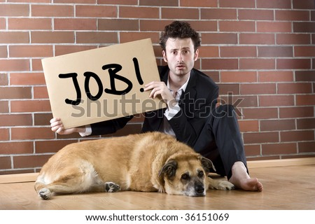 "desperate businessman sits with a dog on the floor and holds a ""Need Job"" sign - stock photo"