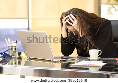 Desperate businesswoman on line worried after bankruptcy in front of a laptop with her hands in the head at office - stock photo