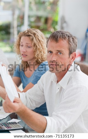 Desperate couple calculating their domestic bills at home - stock photo