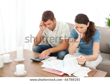 Desperate couple doing their accounts sitting on the sofa at home - stock photo