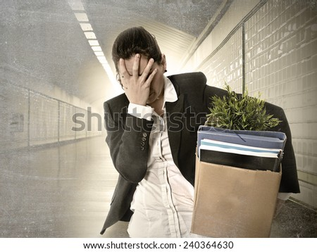 desperate depressed businesswoman fired from job carrying office belongings in cardboard box crying sad in grunge tunnel background in financial crisis and work loss concept - stock photo