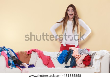 Desperate helpless freaking out woman standing behind sofa couch in messy living room. Young girl surrounded by many stack of clothes. Disorder and mess at home. - stock photo