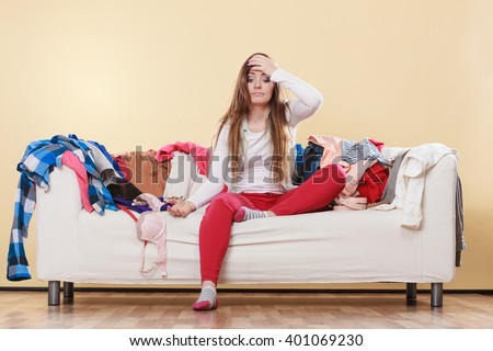 Desperate helpless woman sitting on sofa couch in messy living room with hand on head. Young girl surrounded by many stack of clothes. Disorder and mess at home. - stock photo