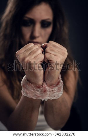 Desperate kidnapped woman tied with rope in dark waiting for help. Selective focus. Focus on the rope. - stock photo