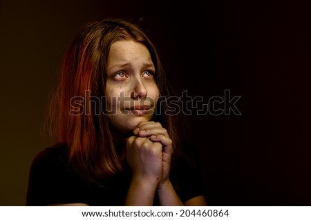 Desperate lonely teen girl praying - stock photo
