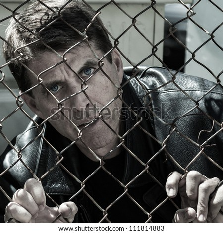 Desperate looking man gripping a wire fence.