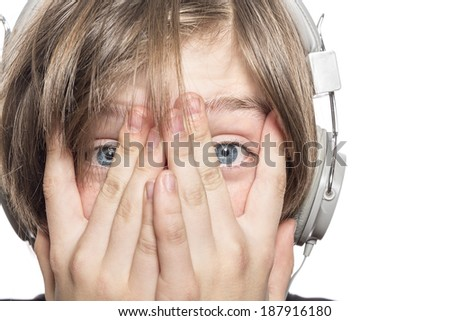 desperate male teenager with headphones covering his face with hands, isolated on white - stock photo