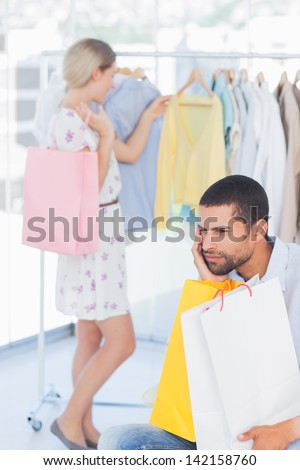 Desperate man being bored while his wife is shopping in boutique - stock photo