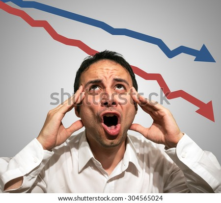 Desperate man in front of falling arrows, financial crisis concept - stock photo