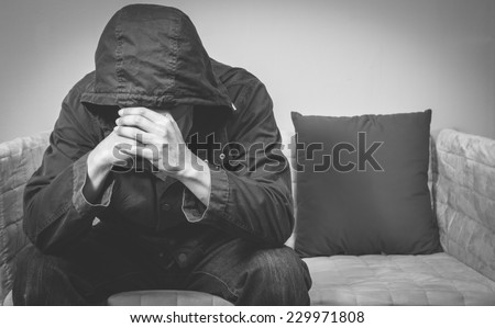 Desperate mystery man sit on armchair next to backrest pillow. feel sad ,headache and alone / emotion concept  - stock photo