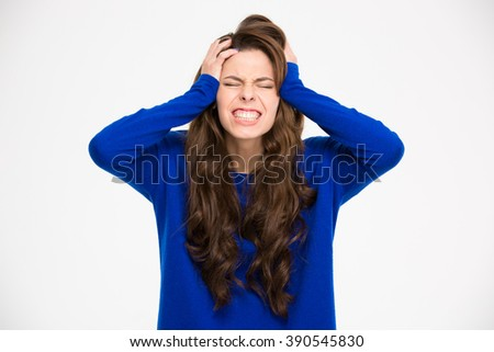 Desperate pretty young woman with hands on head suffering from headache over white background  - stock photo