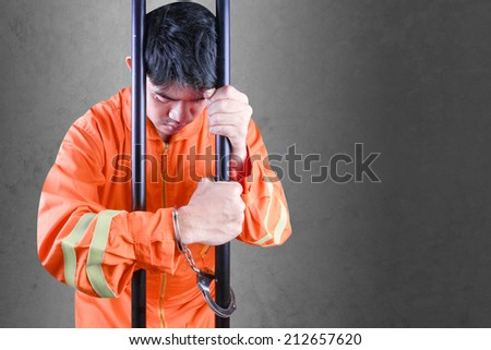 Desperate prisoner a handcuffed in jail holding bars against dark room concrete wall - stock photo