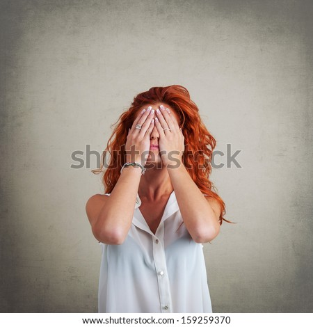 Desperate redhead woman portrait against grunge background.  - stock photo