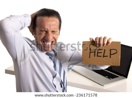 desperate senior businessman in crisis working on computer laptop at office desk in stress under pressure facing work problems asking for help isolated on white background - stock photo