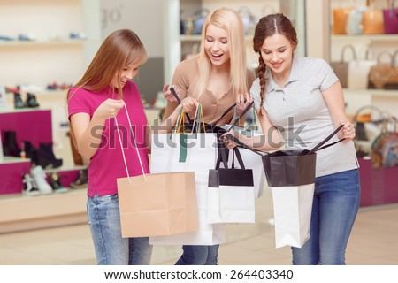 Desperate shopping women. Three beautiful young women smiling with excitement while looking inside their shopping bags copyspace - stock photo