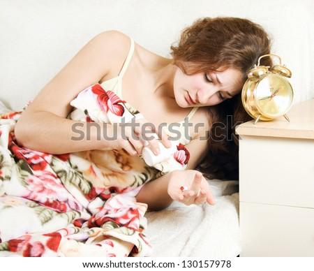 Desperate sleepless woman taking sleeping pills and yawning - stock photo